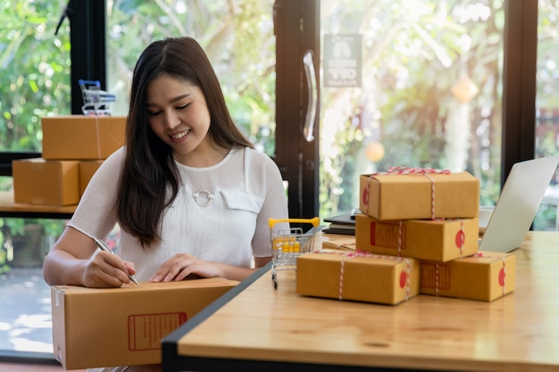 Mulher de negócios com vendas on-line e envio de encomendas em seu escritório em casa.