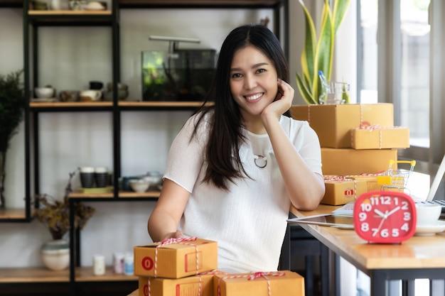 Mulher de negócios com vendas onlines e transporte do pacote em seu escritório domiciliário.