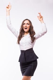 Mulher de negócios comemorando feliz alegre em terno branco em todo o corpo. torcendo o vencedor em uma dança alegre sobre o sucesso. jovem empresária caucasiana isolada na parede branca