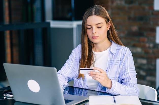 Mulher de negócios concentrada, de cabelos escuros, verifica sua conta bancária em um laptop e tem um cartão de crédito