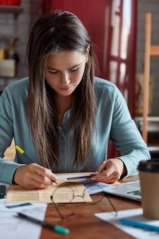 Mulher de negócios concentrada examina papéis, faz projeto de inicialização, segura cartões plásticos, anota número