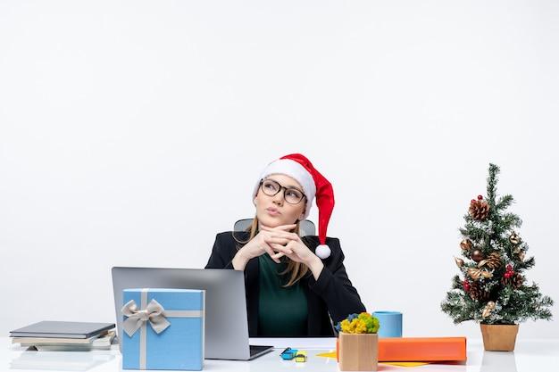 Mulher de negócios concentrada positiva com seu chapéu de papai noel, sentada à mesa com uma árvore de natal e um presente nela e pensando em algo sobre fundo branco