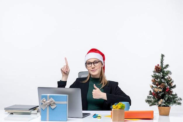 Mulher de negócios confiante com chapéu de papai noel sentada a uma mesa com uma árvore de natal e um presente nela fazendo um gesto de ok e apontando algo no escritório sobre fundo branco