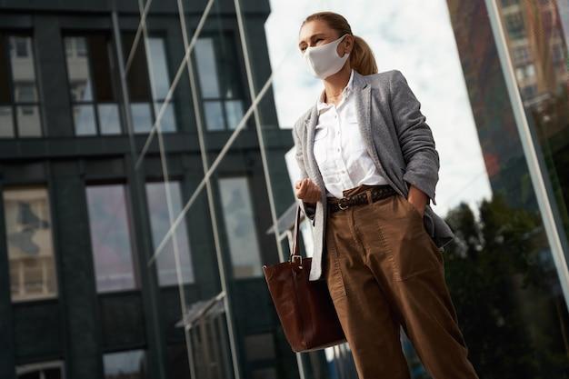 Mulher de negócios confiante com proteção covid usando máscara protetora em pé perto do escritório