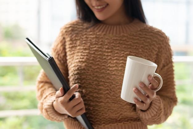 Mulher de negócios confiante conteúdo segurando a caneca e pasta