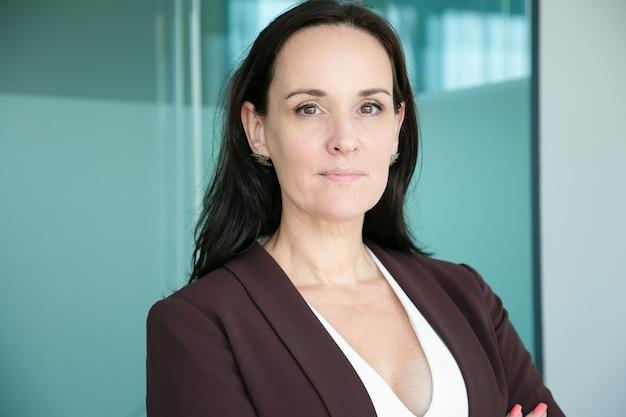 Mulher de negócios confiante e positiva usando terno formal e com os braços cruzados