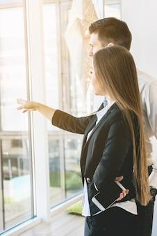 Mulher de negócios confiante mostra algo de muito longe para o windows ao encontrar colegas de trabalho.