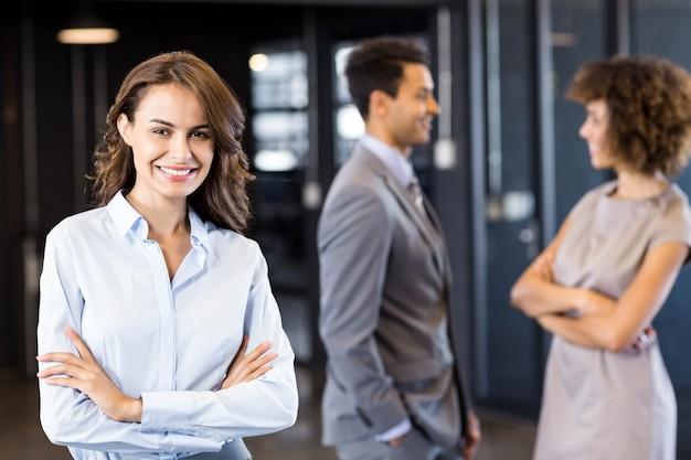 Mulher de negócios confiante no escritório com seus colegas de trabalho