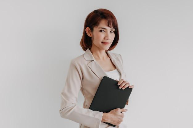 Mulher de negócios confiante segurando um tablet isolado no fundo branco