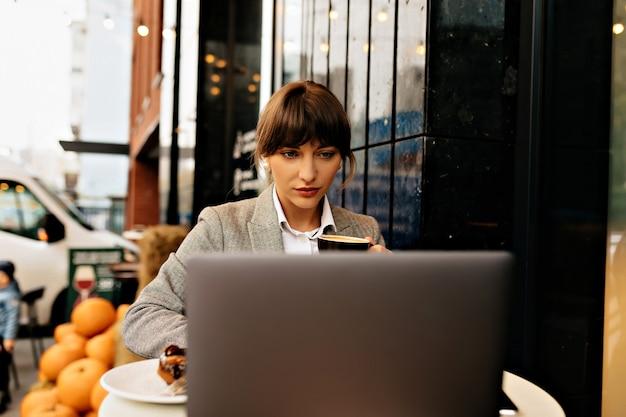 Mulher de negócios confiante trabalhando no laptop na rua café, digitando no teclado, senhora esperta, sério, olhando na tela.