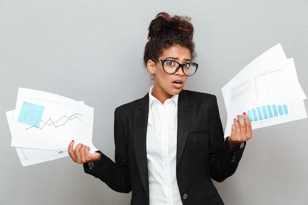 Mulher de negócios confusa africana com documentos de diagramas