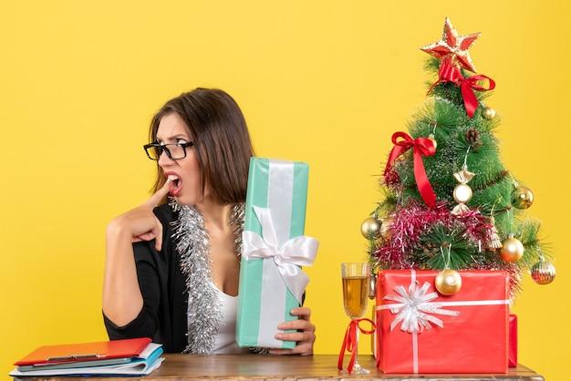 Mulher de negócios confusa de terno com óculos mostrando seu presente de forma surpreendente e sentada em uma mesa com uma árvore de natal no escritório