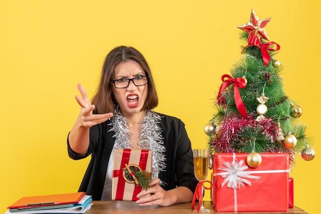 Mulher de negócios confusa, de terno com óculos, segurando seu presente, perguntando algo e sentada em uma mesa com uma árvore de natal no escritório