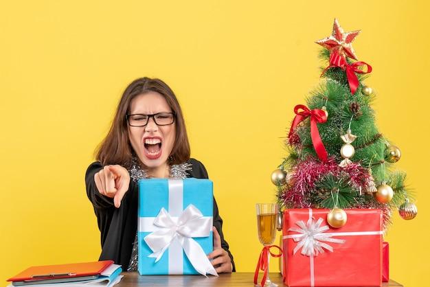 Mulher de negócios confusa emocional, de terno com óculos, segurando seu presente, gritando com alguém e sentada em uma mesa com uma árvore de natal no escritório