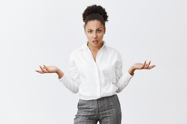 Mulher de negócios confusa não consegue entender o que está acontecendo, encolhendo os ombros frustrada