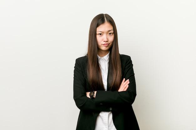 Mulher de negócios consideravelmente chinesa nova que olha infeliz com expressão sarcástica.