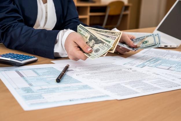 Mulher de negócios conta dólares, no formulário fiscal 1040