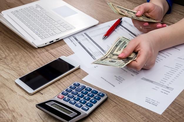 Mulher de negócios conta notas de dólar.