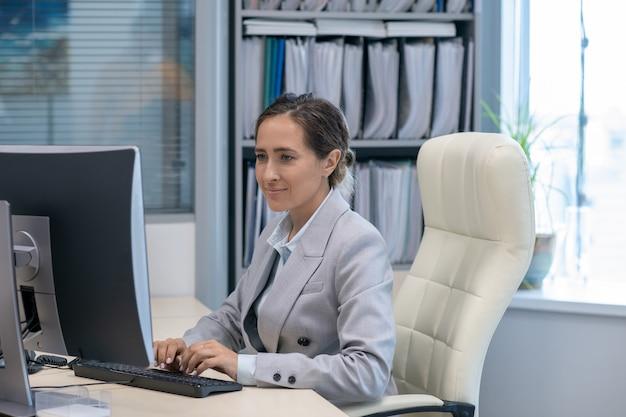 Mulher de negócios contemporânea trabalhando na frente do computador