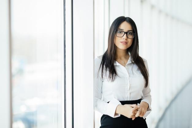 Mulher de negócios cruzou o retrato de mãos no escritório com janelas panorâmicas. conceito de negócios