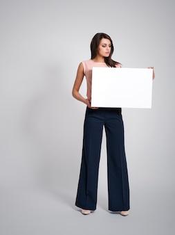 Mulher de negócios curiosa com quadro branco vazio