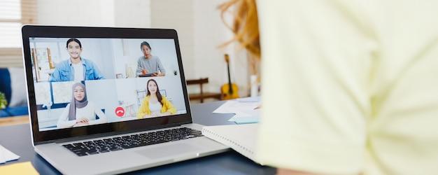Mulher de negócios da ásia usando laptop conversa com colegas sobre o plano de uma reunião de videochamada enquanto trabalha em casa na sala de estar. auto-isolamento, distanciamento social, quarentena para prevenção do vírus corona.