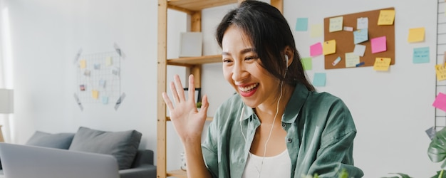 Mulher de negócios da ásia usando laptop conversa com colegas sobre o plano de videochamada enquanto inteligente trabalhando em casa na sala de estar.