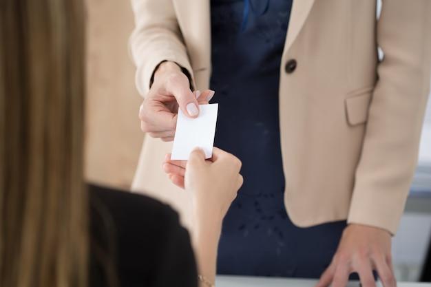 Mulher de negócios dando seu businesscard para o parceiro. reunião de negócios, convite, parceria ou conceito de contratação.