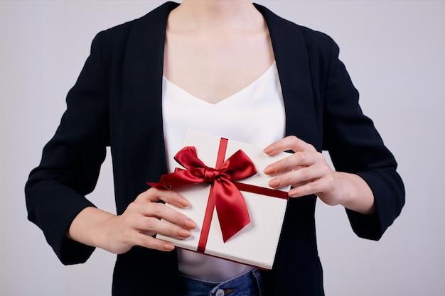 Mulher de negócios de aparência agradável está de pé em cinza em uma jaqueta preta, camiseta branca. não precisa trabalhar.