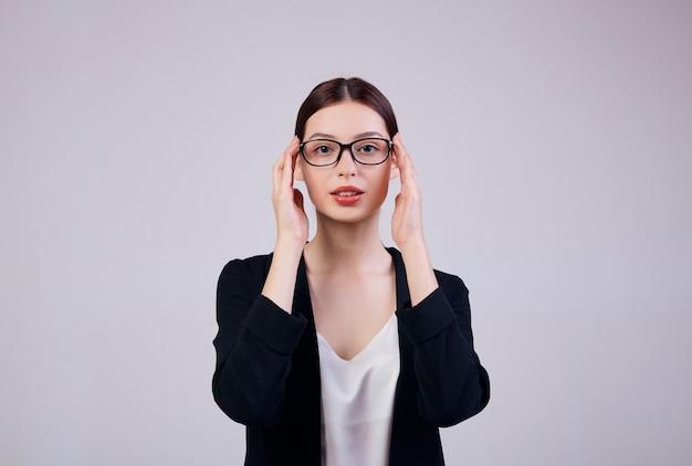 Mulher de negócios de aparência agradável está de pé em cinza em uma jaqueta preta, camiseta e óculos de computador.