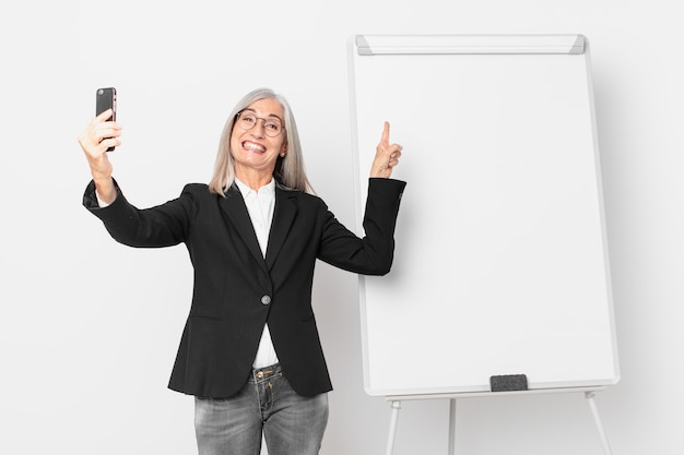 Mulher de negócios de cabelo branco de meia-idade com um espaço vazio da cópia do tabuleiro.