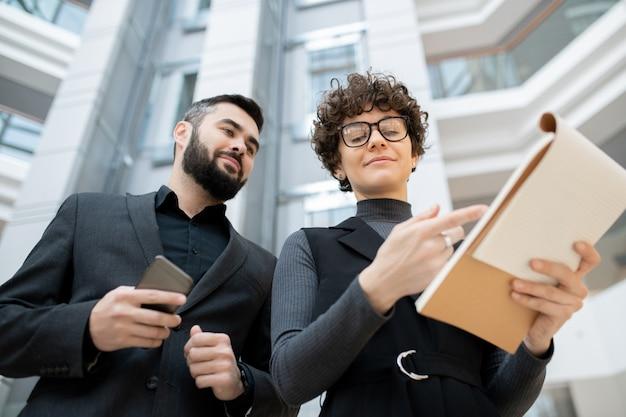 Mulher de negócios de cabelo encaracolado de óculos apontando para a área de transferência enquanto explica a estratégia de desenvolvimento para um colega