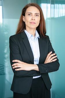 Mulher de negócios de cabelo sério e confiante, vestindo jaqueta, em pé com os braços cruzados