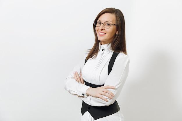Mulher de negócios de cabelos castanhos bonita caucasiana jovem sorridente de terno preto, camisa branca e óculos de mãos cruzadas, isolado no fundo branco. gerente ou trabalhador. copie o espaço para anúncio.