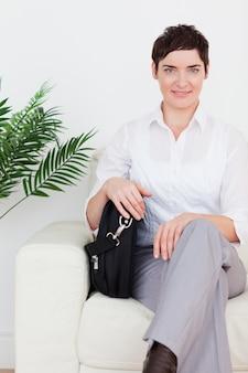 Mulher de negócios de cabelos curtos sentado em um sofá
