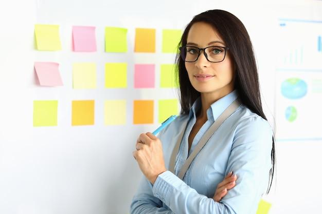 Mulher de negócios de camisa azul e óculos fica perto do quadro-negro com uma caneta na mão e sorri.