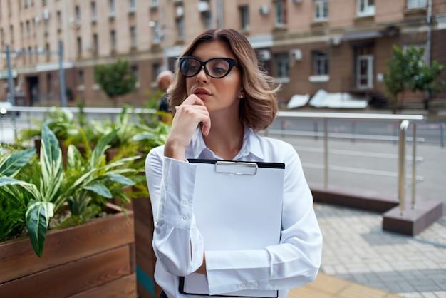 Mulher de negócios de camisa branca na rua com documentos de trabalho