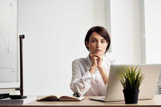 Mulher de negócios de camisa branca sentada à mesa de trabalho em frente ao escritório do laptop