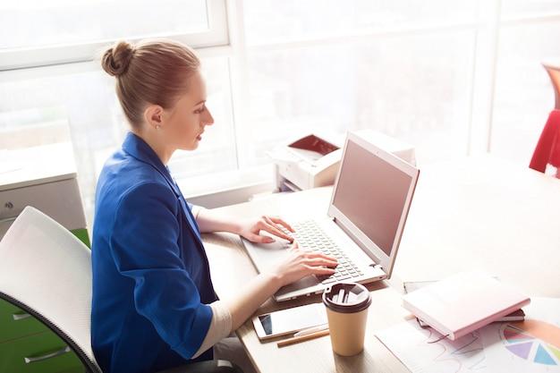 Mulher de negócios de casaco azul, sentado à mesa perto da janela brilhante e trabalhando