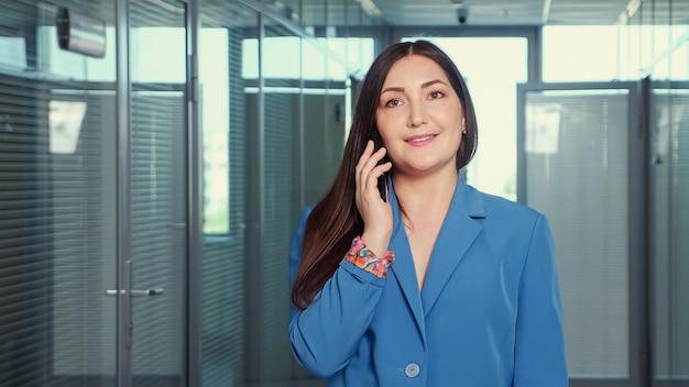 Mulher de negócios de casaco clássico azul fala no smartphone