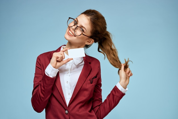 Mulher de negócios de jaqueta vermelha e óculos segurando um cartão