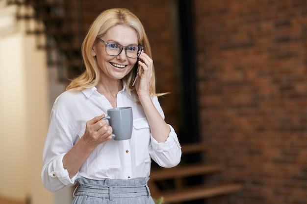 Mulher de negócios de meia idade com bom dia, cabelo loiro e óculos, segurando uma xícara de café ou chá