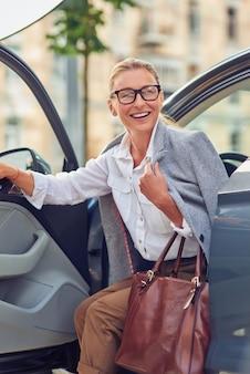 Mulher de negócios de meia-idade na moda bem-sucedida com bolsa saindo de seu carro moderno e