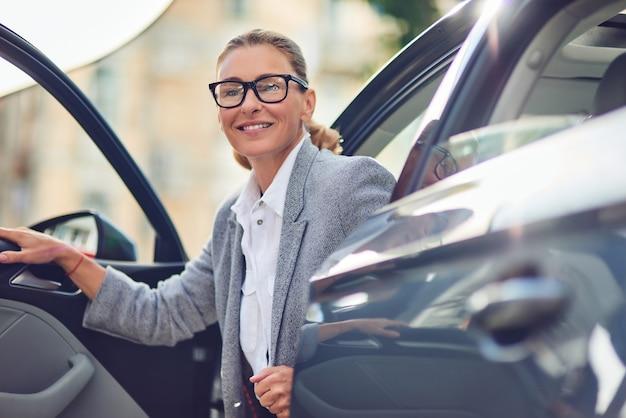 Mulher de negócios de meia-idade positiva e bem-sucedida em roupas clássicas saindo de seu carro moderno