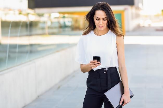 Mulher de negócios de meia idade que trabalha com seus telefone e portátil espertos ao ar livre.