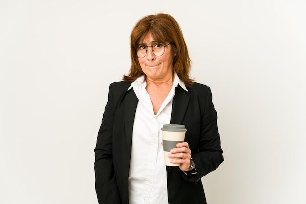 Mulher de negócios de meia idade segurando um café para viagem isolado confuso, sente-se em dúvida e inseguro.