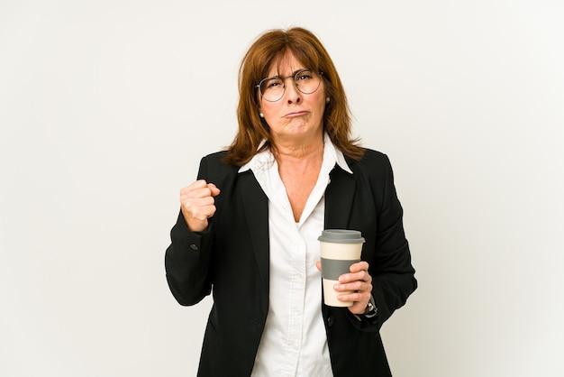 Mulher de negócios de meia-idade segurando um café para viagem isolado e mostrando o punho para a frente