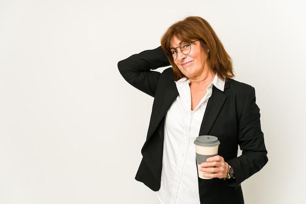Mulher de negócios de meia idade segurando um café para viagem isolado tocando a parte de trás da cabeça, pensando e fazendo uma escolha.