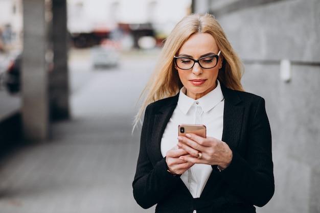 Mulher de negócios de meia idade usando telefone fora do centro de negócios