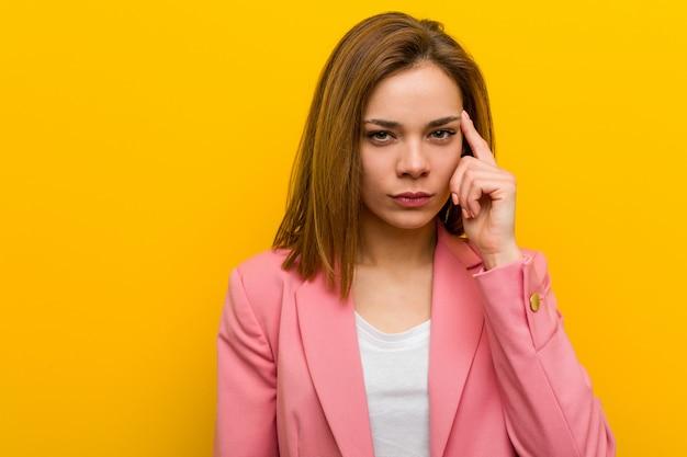Mulher de negócios de moda jovem apontando seu templo com o dedo, pensando, focado em uma tarefa.
